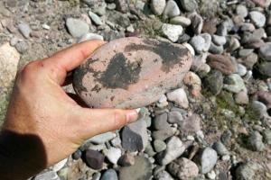 Black desert varnish unevenly coating alluvial gravel
